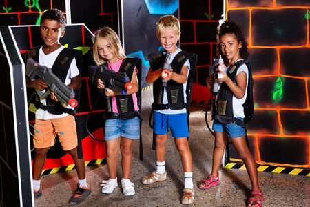 Cheerful tween girls and boys of different nationalities with laser pistols posing together in dark laser tag labyrinth Фото со стока