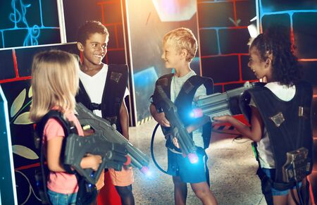 Modern preteen girls and boys of different nationalities with laser pistols playing laser tag on dark labyrinth