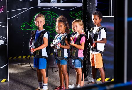 Cheerful tween girls and boys of different nationalities with a laser pistols posing together at a dark laser tag labyrinth