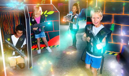 Modern preteen girls and boys of different nationalities with laser pistols playing laser tag at dark labyrinth Фото со стока