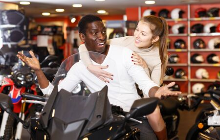 Portrait of happy couple posing on new purchased motorcycle in bike store Banco de Imagens