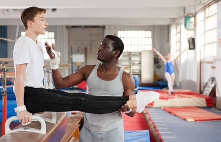 Active African male coach helping teenage boy doing gymnastic exercises on equipment