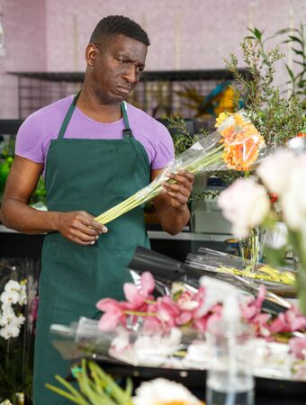 African American man owner of flower shop looking dissatisfied and worried with state of flowers 写真素材