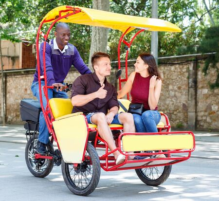 Young loving cheerful positive smiling couple enjoying tour of city on trishaw with affable African American driver Archivio Fotografico - 129470634