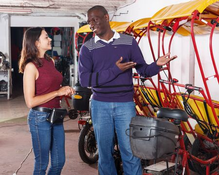 African American male driver of bikecab offering  city  tour to young woman Archivio Fotografico - 129470700