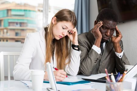 Frustrated business team working with papers and computer in modern office