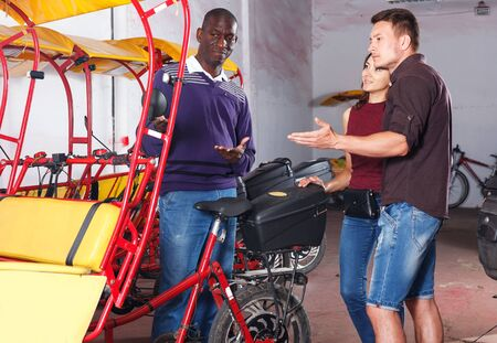 Successful African American driver of pedicab offering touristic tour of city to young loving couple Archivio Fotografico - 129470753