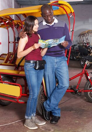 Young international couple standing near cycle rickshaw for touristic tour of city Archivio Fotografico - 129470770