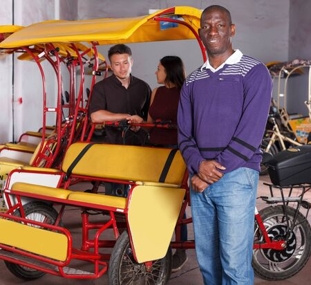 Smiling African-American pedicab driver offering  rickshaw cycle tour Archivio Fotografico - 129470833