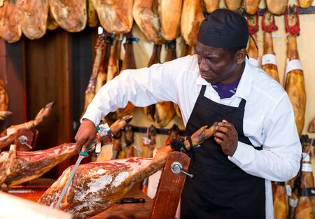 African American seller slicing jamon fixed on jamonera, preparing for sale