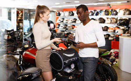 Positive glad pleasant couple looking for new duffel bag for motorcycle in shop of moto equipment