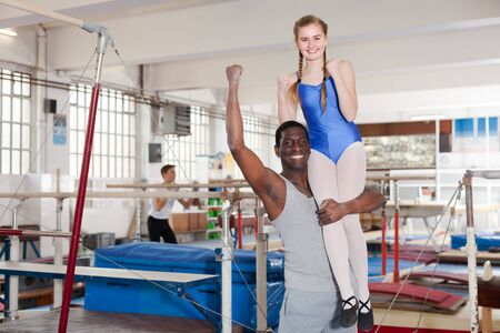African male coach and teenage girl exulting sporting achievements at acrobatic hall