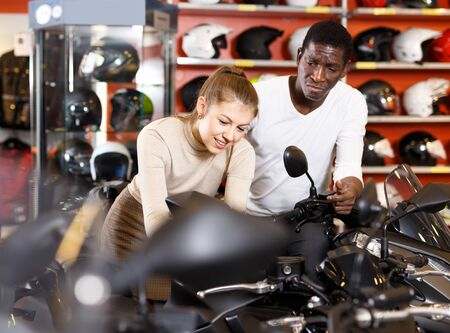 Portrait of enthusiastic man and woman together looking new motorbike at motosalon showroom Banco de Imagens