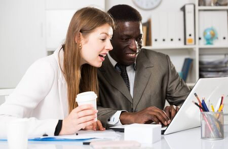 Positive business man and woman working with computer in modern office