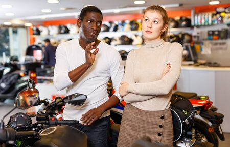 Young pleasant couple looking for new motorcycle in salon, dissatisfied angry unhappy woman expressing displeasure