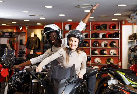 Happy adult man and woman in helmets sitting together on new motorcycle in store and having fun