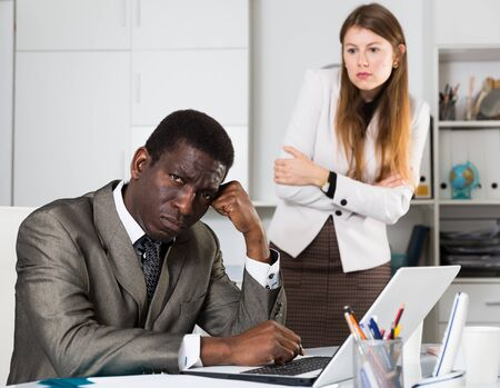 Tired man manager sitting at table and angry woman boss on background