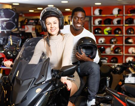 Cheerful positive  young couple satisfied with choice in modern motorcycle salon