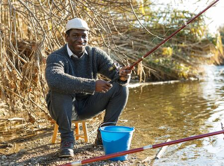 Portrait of cheerful afro fisherman sitting on wooden stool and fishing