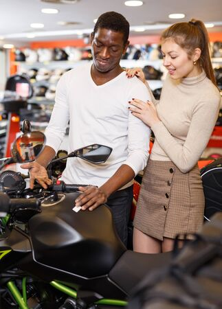 Portrait of young smiling man and woman together looking new motorbike at motosalon showroom Banco de Imagens