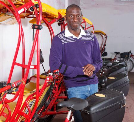 Successful African American driver of pedicab offering touristic tour Archivio Fotografico - 129471000