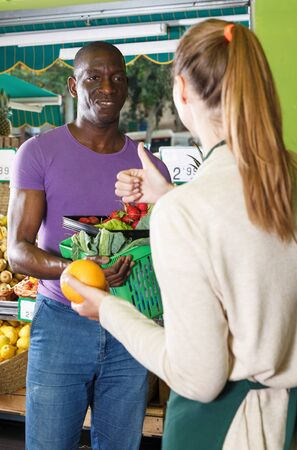 Seller woman is helping man choose exotic fruits in the market. Banque d'images - 129470959