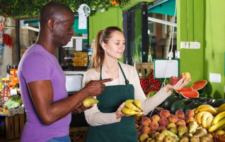 Male client is asking from seller female about freshness fruits in the market Banque d'images - 129471007