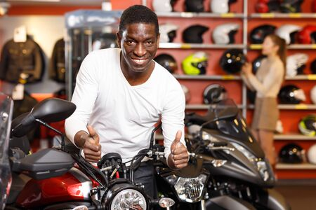 Glad Afro American man posing near new purchased motorcycle in bike salon