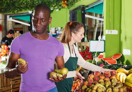 Male customer is asking from seller female about freshness fruits in the market Banque d'images - 129470868