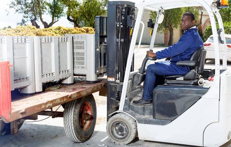 African American male driver using forklift for unload boxes with grapes at winery outdoor