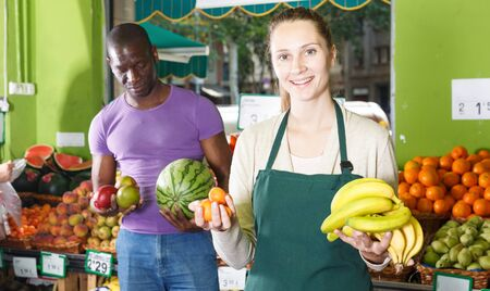 Smiling female seller is helping male client choose fresh fruits in the market. Banque d'images - 129470811