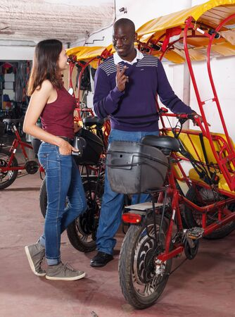 Successful African American driver of bikecab offering touristic tour of city to young woman Archivio Fotografico - 129470728