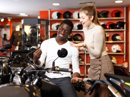 Portrait of cheerful couple posing on new purchased motorcycle in bike shop