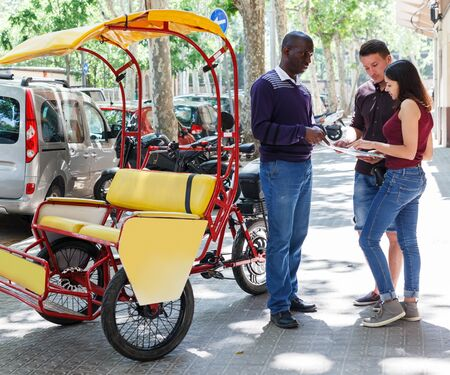 Positive African American driver of rickshaw offering touristic tour of city to young loving couple Archivio Fotografico - 129470686
