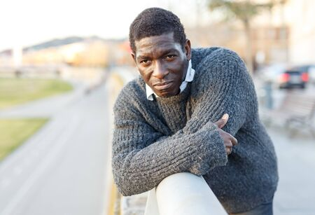 Portrait of cheerful African-American man in warm sweater in urban environment