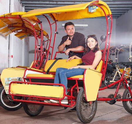 Portrait of happy young couple planning to hire cycle rickshaw for touristic tour of city Archivio Fotografico - 129470582