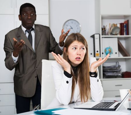 Upset business woman sitting at laptop in office on background with angry colleague