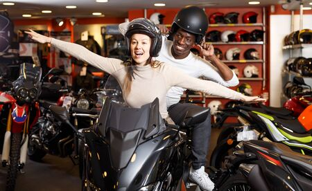 couple having fun together at motorcycle salon after buying new bike