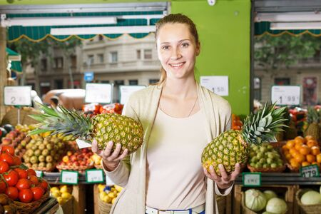 Portrait of woman who is holding pineapples in the fruit market. Banque d'images - 129470592