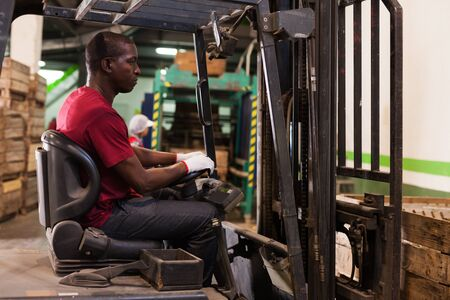 Portrait of concentrated Afro male driver working on forklift in fruit warehouse
