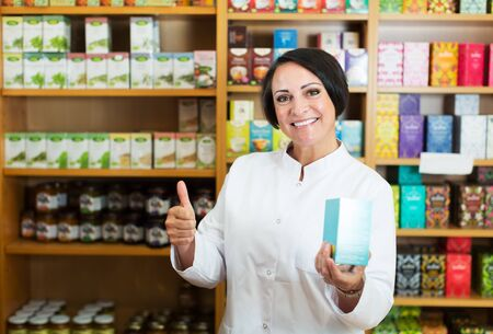 Portrait of happy mature female pharmacist with biologically active dietary supplement package