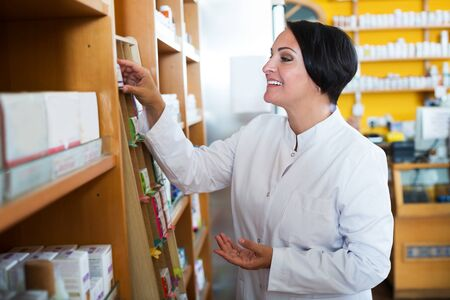 Portrait of positive mature female pharmacist in biologically active dietary supplements store