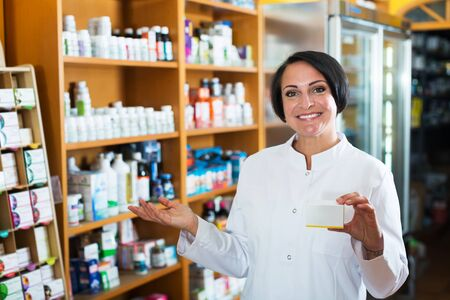 Portrait of happy mature pharmacist woman with biologically active dietary supplement package in store