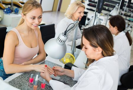 Two glad  positive women clients having manicure done in nail salon 写真素材