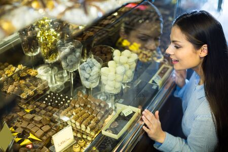 brunette woman selecting fine chocolates and confectionery at cafe display