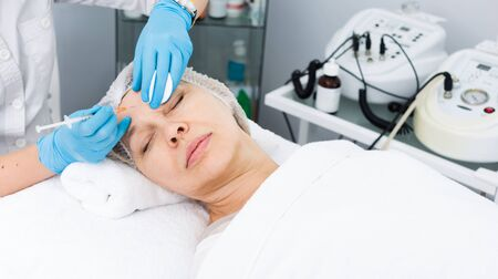 Young female doctor using injection in beauty procedures to woman client Stockfoto