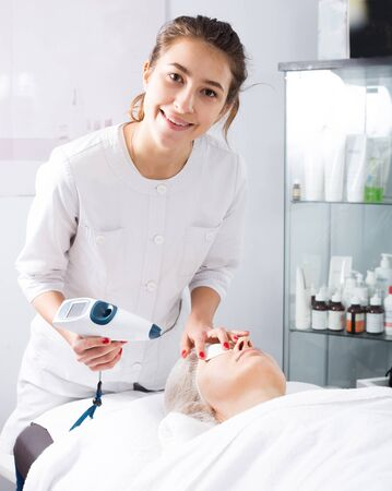 Aged female patient making beauty procedures for face in spa salon