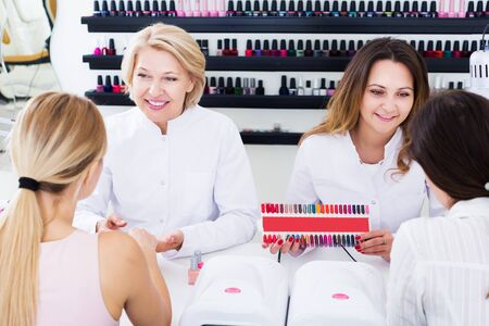 Two smiling women manicurists manicuring female clients in nail salon