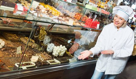 Cheerful positive seller with dark and white chocolates confectionery at display