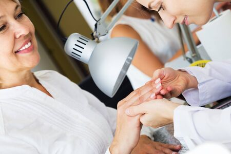 Mature woman client having manicure done in nail salon in close-up Stockfoto